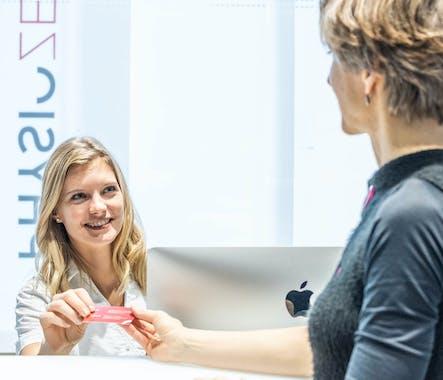 Praxisassistentin überreicht einer Patientin die Terminkarte